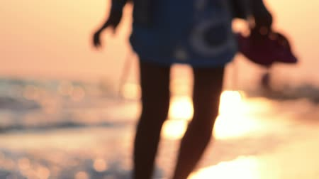 Evening sunset on the ocean. Rest at the seaside resort. Hot summer evening by the sea. Girl walking along the coastline. Close season. Stock mozgókép