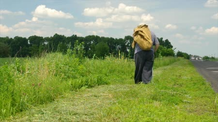 Senior Ukrainian peasant with walking stick carrying heavy sack moving on a roadside at summer season