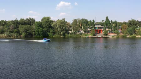 Summer scene with small boat running on a Dnepr river in center of Dnepr city, Ukraine