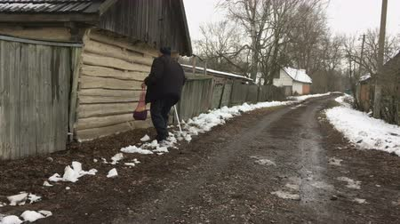 Senior Ukrainian peasant with walking stick carrying string-bag moving on a winter street in Ukrainain village Vídeos