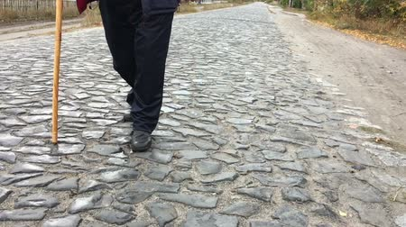 Overweight man walking on a cobblestone road (slow filming) Vídeos