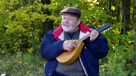 Positive Ukrainian senior man singing while playing mandolin and sitting on clearing in autumnal forest Vídeos