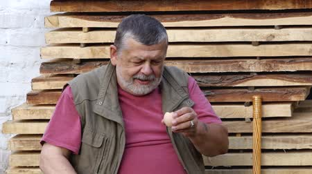 Senior man drinking raw hen`s egg while sitting outdoor against pile of boards