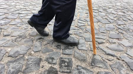 Man walking on a cobblestone road (slow filming, side view) Vídeos