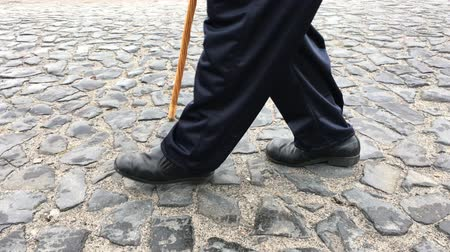utdoor : Man walking on a cobblestone road (close-up, slow filming, side view)