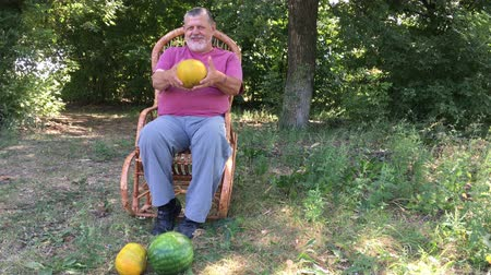 vime : Ukrainian senior farmer shows his organic harvest while sitting in a wicker chair