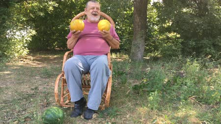 Ukrainian senior farmer shows two melons while sitting in a wicker chair outdoor