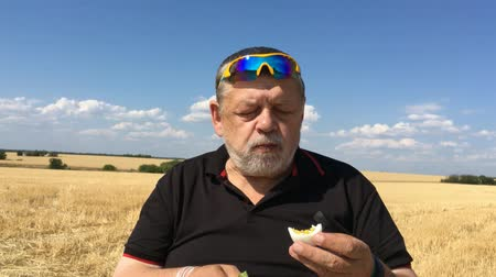 Ukrainian senior farmer eating cucumber and boiled egg while sitting outdoor against harvested wheat field and blue sky