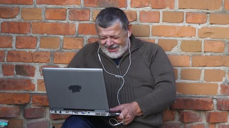 glinka : Bearded senior man looking at notebook screen and laughing while sitting outdoor against brick wall