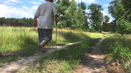 Overweighted senior man walking away on an summer earth path barefoot