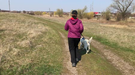 Woman running with mixed breed white dog on an earth road at spring season