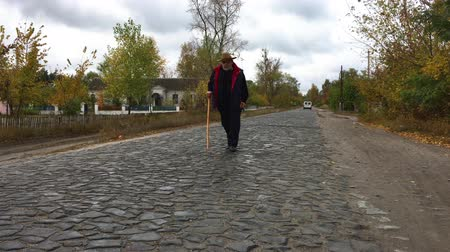 godo : Overweight man with walking stick walking on a cobblestone road at cloudy autumnal day