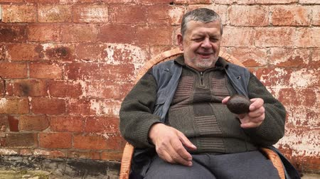 Ukrainian senior peasant scrutinizing avocado Hass for the first time in the life while sitting in a wicker chair against brick wall