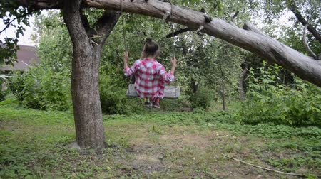 girl swinging on rope garden swing under fallen tree by summer, slide camera movement