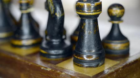 vintage chess set up on chessboard with focus on rook, sliding and pan camera movement