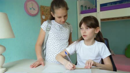 воспитание : two caucasian girls doing homework discussing lessons. pupils studying at home. one girl helping another