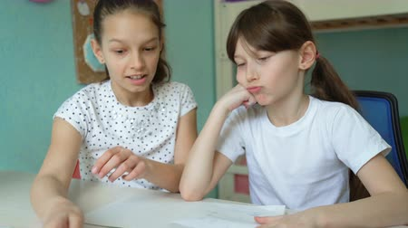 uygulanması : older girl helping her sister homework. children learning exercises together at home