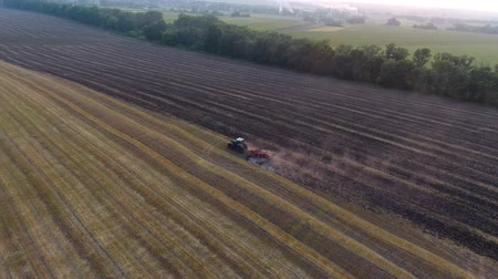 fertilizing : aerial farmer preparing land seedbed cultivator in farmlands agriculture lonely tractor plowing field. Agricultural work and cultivation processing. Stock Footage