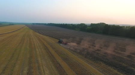 ploughing : Agricultural machinery plowing farming field. Aerial view cultivation. Tractor preparing soil