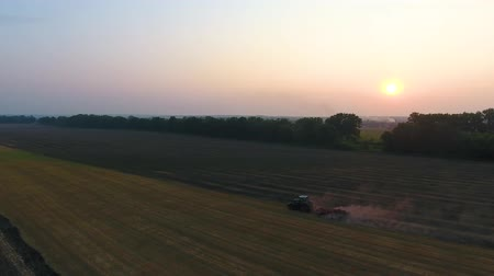 fertilizing : Agricultural machinery plowing farming field at sunset. Aerial view cultivation. Tractor preparing soil