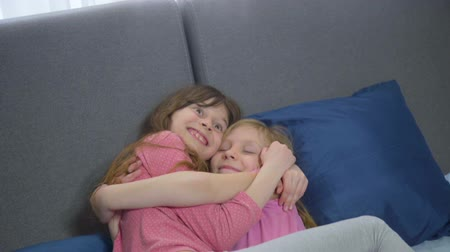 két : funny sisters fooling around on bed. two girls hugging and clinch each other. funny faces and pose Stock mozgókép