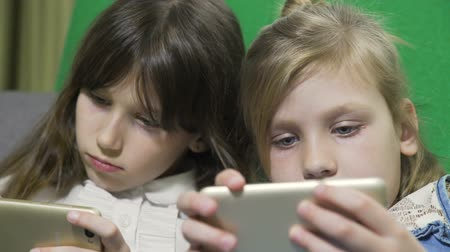 school children : sisters playing in gadgets in bed at home. digital modern gadgets and device addiction. young girls surfing and browsing on smartphones Stock Footage