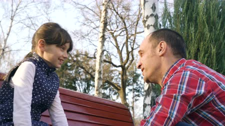 obuwie : father speaking daughter on bench in park closeup. leisure time. parental care. family relations and support