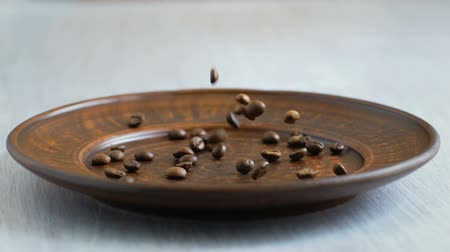 аромат : cheerful morning or day. Roasted Coffee beans falling plate. Slow motion