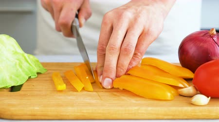 tábua de cortar : Slicing sweet pepper on wooden cutting board. Male hands cut with knife bell pepper.