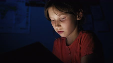 cobertor : Dolly shot caucasian girl lying in bed playing tablet in social internet in dark blue light under blacket. Childhood, communication and technology concept