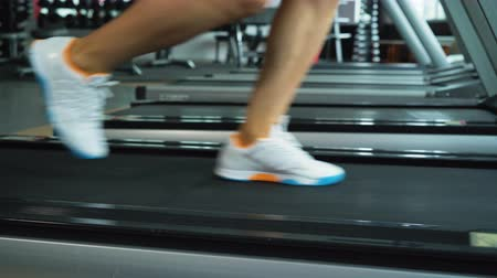 tornacipő : Closeup shot of womans legs running on treadmill at the gym, fitness club. Health, sport and cardio workout concept Stock mozgókép
