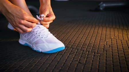 assentado : Fit woman seated on the floor of a gym tying shoelaces sneakers. Healthy lifestyle. Sport and cardio workout concept