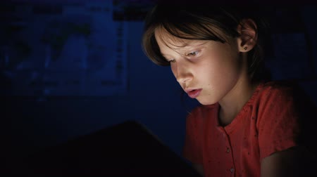mobile game : Dolly shot caucasian girl lying in bed playing tablet in social internet in dark blue light under blacket. Childhood, communication and technology concept