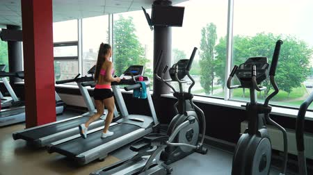 treadmill : Young woman training in fitness club, gym and sport activity. Female working out and running on treadmill, athlete with wellness equipment. Health, sport and cardio workout concept