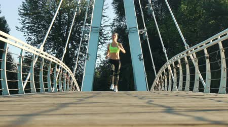 mosty : Active woman jogging running on city footbridge. Exercising outdoors slow motion. Attractive fit girl training on bridge morning. Healthy, fitness, wellness lifestyle. Sport, cardio workout concept
