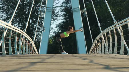 fitness tracker : Active woman exercising and stretching in city park on footbridge. Attractive fit girl training warming up at morning outdoors. Healthy, fitness, wellness lifestyle. Sport, cardio, workout concept