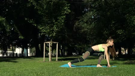 fitness tracker : Active woman exercising and stretching yoga in city park on grass. Attractive fit girl training warming up at morning outdoors. Healthy, fitness, wellness lifestyle. Sport, cardio, workout concept