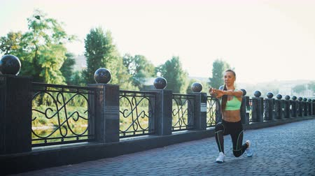 fitness tracker : Active woman exercising and stretching in city park. Attractive fit girl training warming up at morning outdoors. Healthy, fitness, wellness lifestyle. Sport, cardio, workout concept Stock Footage