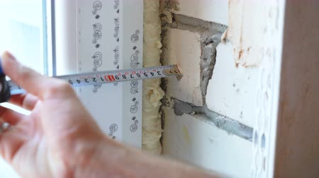 genişlik : Closeup man hands checking distance between window and wall with measure tape. Repairs, building, design concept Stok Video