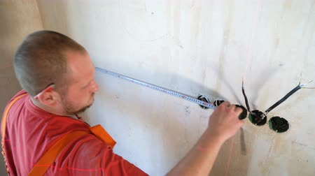 red tape : Electrician checking technical parameters with measure tape and red beam laser tool on building site. Worker controls installed wiring junction box on concrete wall. Safety policy, repair concept Stock Footage