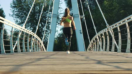mosty : Active woman jogging running on city footbridge back view. Exercising outdoors slow motion. Attractive fit girl training on bridge morning. Healthy, fitness lifestyle. Sport, cardio workout concept