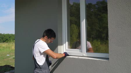 installer : Man worker in safety glasses cleaning surface for metal sill installation. Builder preparing workplace for assembling PVC window construction outside building. Technology, exterior design concept Stock Footage