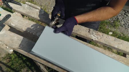 installer : Worker hands in protective gloves preparing PVC window sill for installation cutting metal with scissors closeup. Preparation work on building site. Technology, safety policy, building, repair concept