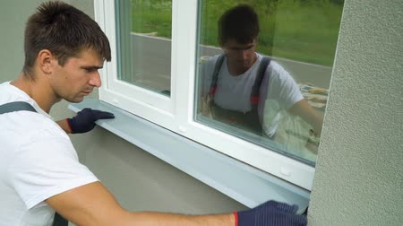 устанавливать : Man worker in protective gloves measuring external frame and PVC window metal sill size. Builder checking components fitting of construction outside building. Technology, exterior design concept Стоковые видеозаписи