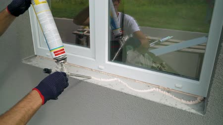 pvc frames : Worker hands in protective gloves applying polyurethane construction foam for window sill installation closeup. Preparation work on building site. Technology, safety policy, building, repair concept