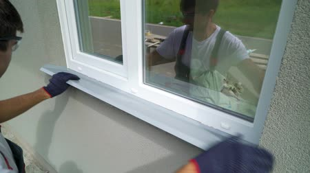 aşağıda : Man worker in safety glasses and protective gloves installing metal sill on external PVC window frame. Window sill installation process. Technology, exterior design, building concept