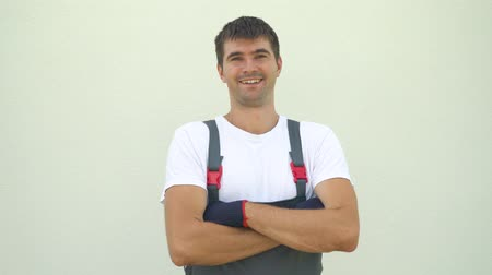 workman : Portrait happy caucasian male industrial worker in work clothes crossing hands looking at camera isolated on light background with free space and copy space. Construction, architect, emotion concept Stock Footage
