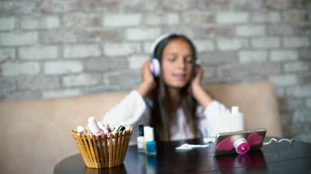 accurate : Blurred cute girl in headphones listening music on phone and singing while making manicure at home with free copy space. Beauty, bodycare, wellness, hygiene, communication, leisure time concept.