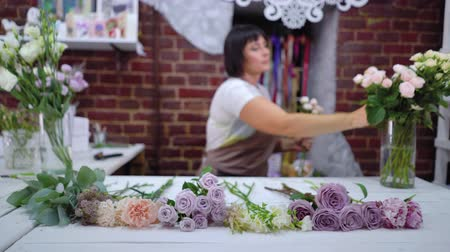designing : Defocused professional caucasian female florist master preparing and selecting rose branches for flower bouquet arrangement in floral design studio. Floristry, handmade and small business concept Stock Footage