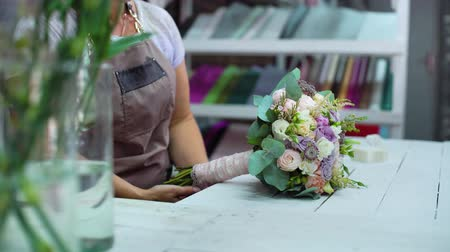 bud rose : professional florist arranging with ribbon wedding bouquet in floral design studio. Caucasian female master in apron creating flower bunch composition. Floristry, handmade and small business concept Stock Footage